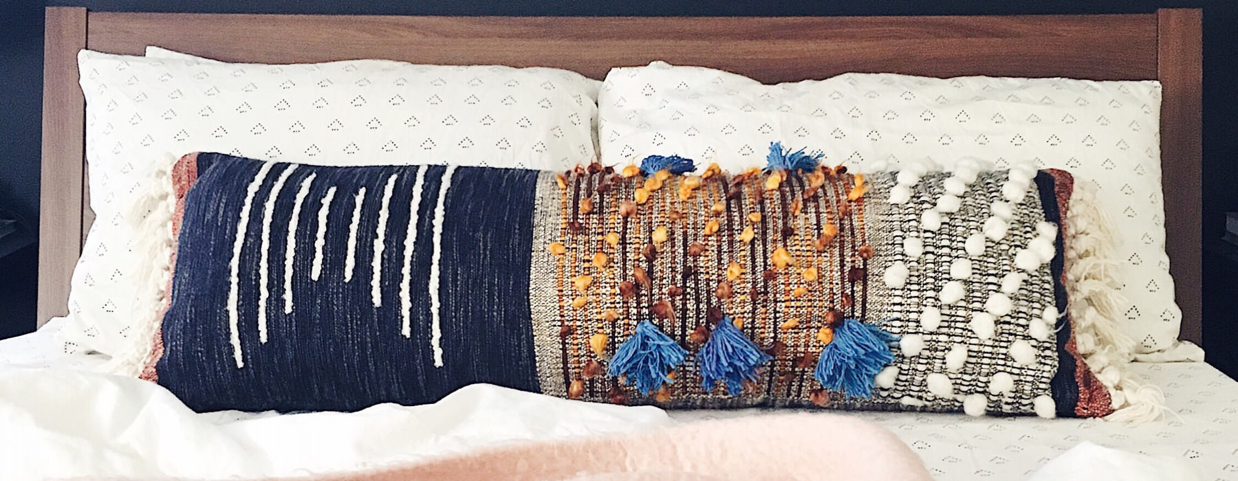 neatly placed pillows on unmade bed with brown, wooden headboard