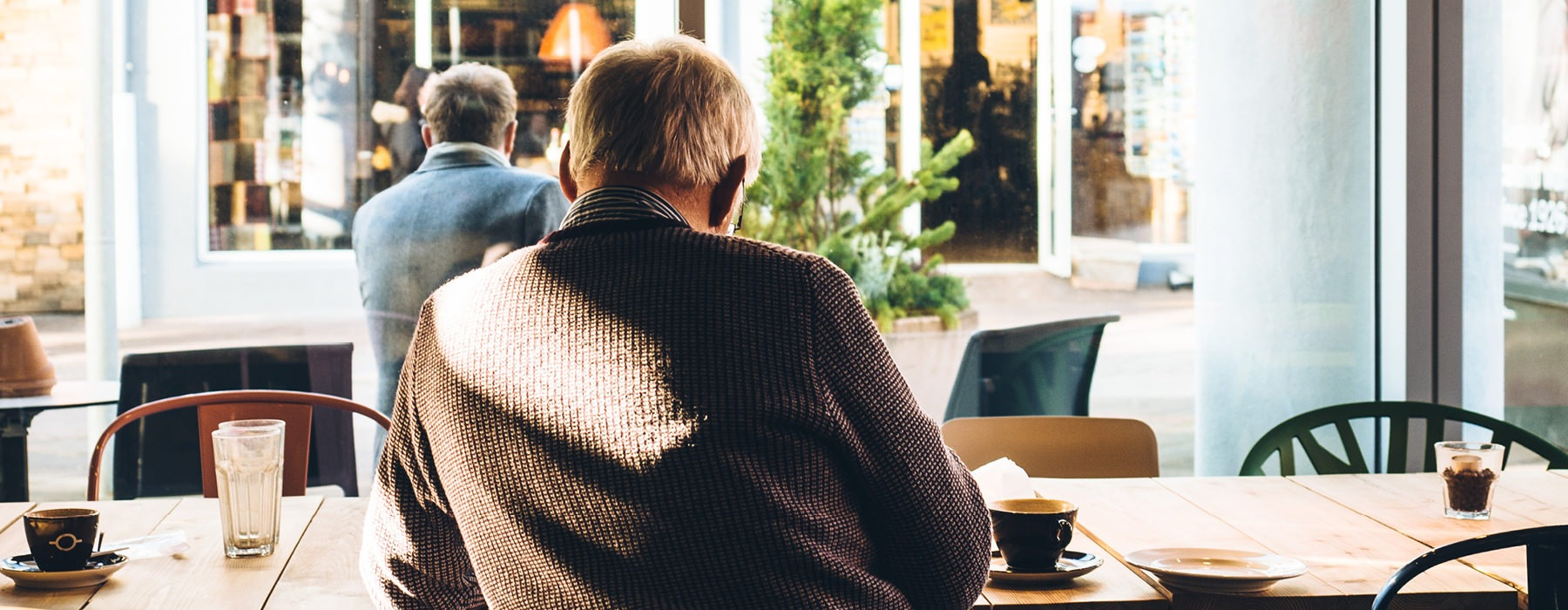 A café with large window. One elderly man sits alone, inside while another sits alone, at table, outside.