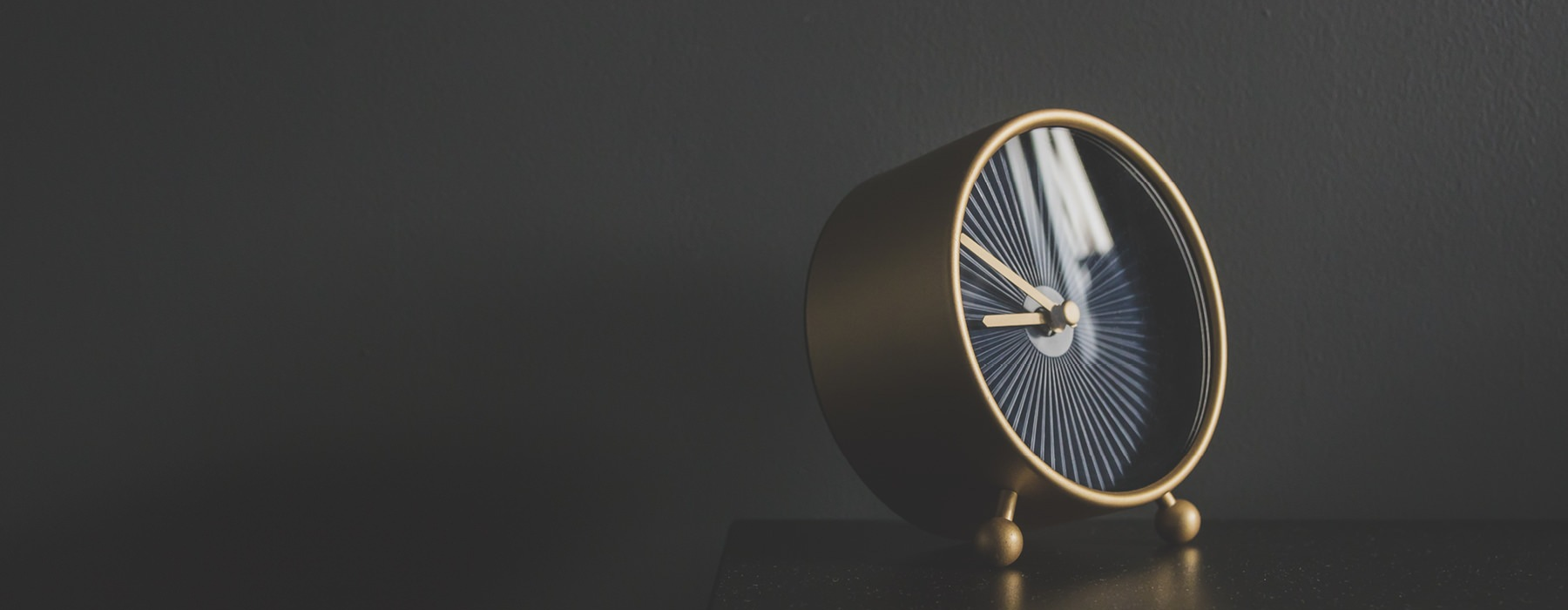 stock photo of round, gold and black clock sitting on a black table against a black wall